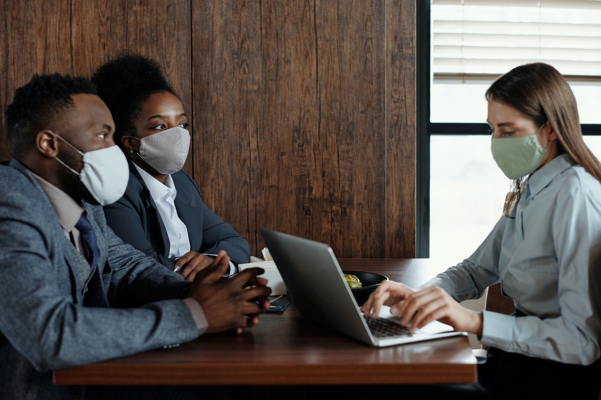 masked couple meeting with masked woman using laptop computer