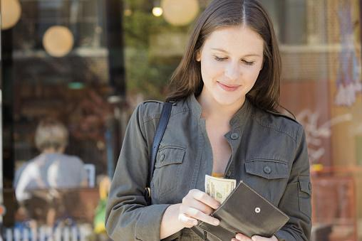 Woman taking cask out of wallet