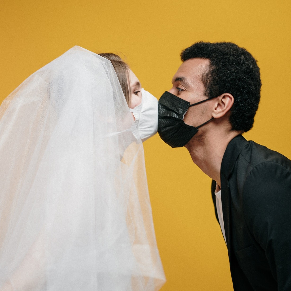 Braide and groom kissing with masks on