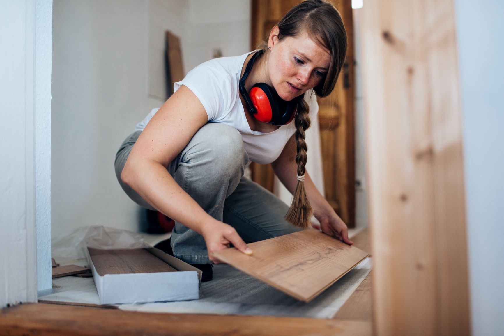 Woman placing wood board on floor.