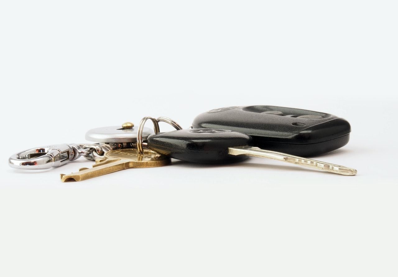 two black and brass colored vehicle keys with fob